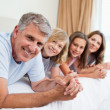 Smiling family lying on the bed — Stock Photo