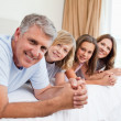 Stock Photo: Cheerful family lying on the bed