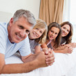Happy family lying on the bed — Stock Photo