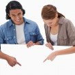 Smiling couple pointing down on blank wall — Stock Photo