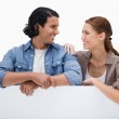 Smiling couple leaning on blank wall — Stock Photo #11214220
