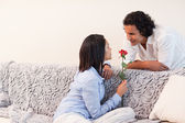 Woman got a rose from her boyfriend in the living room — Stock Photo