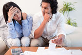 Frustrated couple checking their bills — Stock Photo