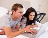 Couple utilisation ordinateur portable dans la chambre à coucher — Photo