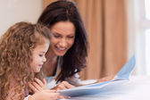 Side view of mother and daughter reading a book together — Stock Photo