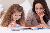 Little girl reading bedtime story with her mother — Stock Photo