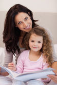 Smiling mother reading a bedtime story with her little daughter — Stock Photo