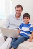 Smiling father and son surfing the internet together — Stock Photo