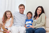 Family sitting on the couch together — Stock Photo