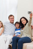Mother taking family photograph on the sofa — Stock Photo
