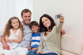 Mother taking family photograph on the couch — Stock Photo