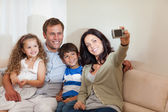 Mother taking family picture in the living room — Stock Photo