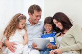 Family using tablet on the sofa — Stock Photo