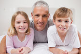 Smiling siblings and their father posing — Stock Photo