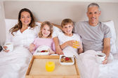 Family having breakfast in a bedroom — Stock Photo
