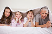 Family lying under a duvet — Stock Photo