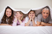 Happy family lying under a duvet — Stock Photo