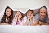 Playful family lying under a duvet — Stock Photo