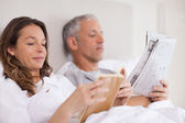 Woman reading a book while her husband is reading the news — Stockfoto