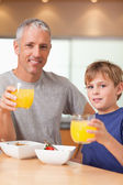 Portrait of a cute boy and his father having breakfast — Stock Photo