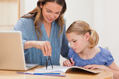 Mother helping her daughter doing her homework — Stock Photo