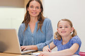 Girl doing her homework while her mother is using notebook — Stock Photo