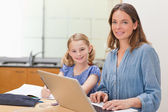 Girl doing her homework while her mother is working with laptop — Stock Photo