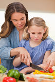 Portrait of a woman slicing pepper with her daughter — Stock Photo