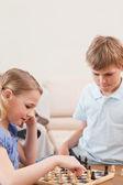 Portrait of siblings playing chess — Stock Photo