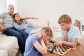 Children playing chess in front of their parents — Stock Photo