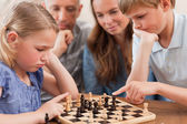 Close up of children playing chess in front of their parents — Foto Stock