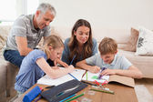 Parents helping their children to do their homework — Stock Photo