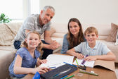 Happy parents helping her children to do their homework — Stock Photo