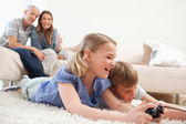 Siblings playing video games with their parents on the backgroun — Stock Photo