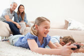 Children playing video games with their parents on the backgroun — Stock Photo