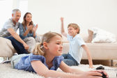 Cute children playing video games with their parents on the back — Stock Photo