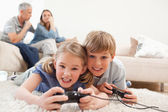 Cheerful children playing video games with their parents on the — Stock Photo