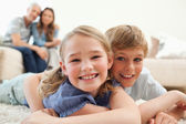 Happy siblings posing on a carpet with their parents on the back — Stock Photo