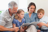 Family reading a book together — Stock Photo
