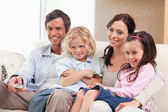 Smiling family watching television together — Stock Photo