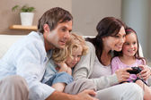 Playful family playing video games together — Stock Photo