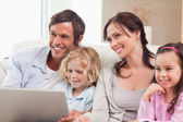 Delighted family using a notebook — Stock Photo