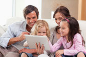 Delighted family using a tablet computer — Stockfoto