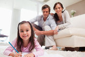 Girl drawing with her parents in the background — Stock Photo