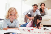 Siblings drawing while their parents are in the background — Stock Photo