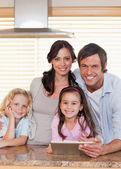 Portrét smějící se rodiny společně pomocí tabletového počítače — Stock fotografie