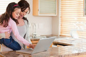 Girl and her mother using a laptop — Stock Photo