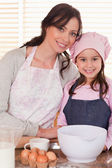 Portrait of a mother and her daughter baking — Stock Photo