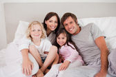 Happy family posing on a bed — Stock Photo