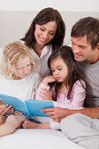 Portrait of a family reading a book — Stock Photo